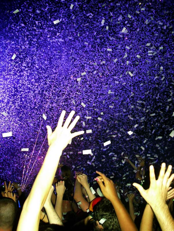 Hands fly through the air while trying to catch the falling confetti at DayGlow March 31. The confetti marked the start of the ÒWord's Largest Paint Party.Ó By Mallory Radtke